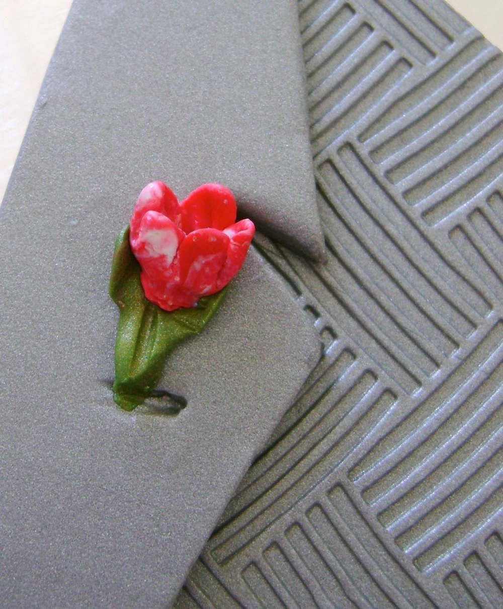 step 15 - Press the boutonniere onto the lapel.  Make a gash for the buttonhole.