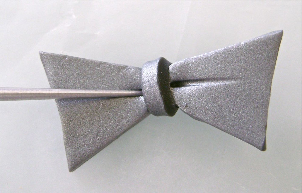 step 16 - Cut a bow tie shape from the clay and wrap a thin piece around the center.  Use an Etch 'n Pearl tool to add detail.