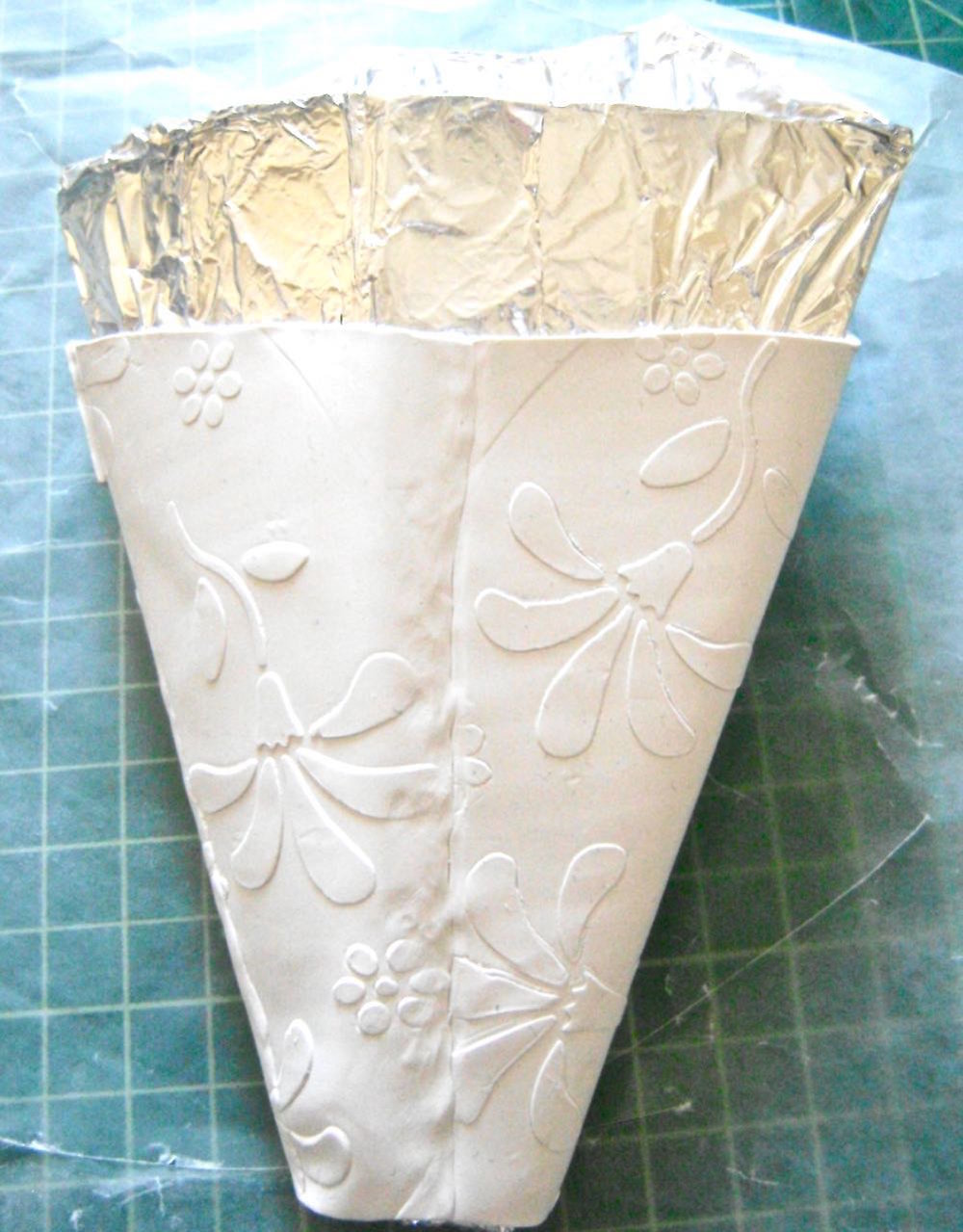 step 10 - Lift the joined sconce pieces off the work surface, peeling away the wax paper.  Wrap the clay sconce around the mold.  The center of the sconce should match the center of the mold.  Blend the back seam using sculpting tools.