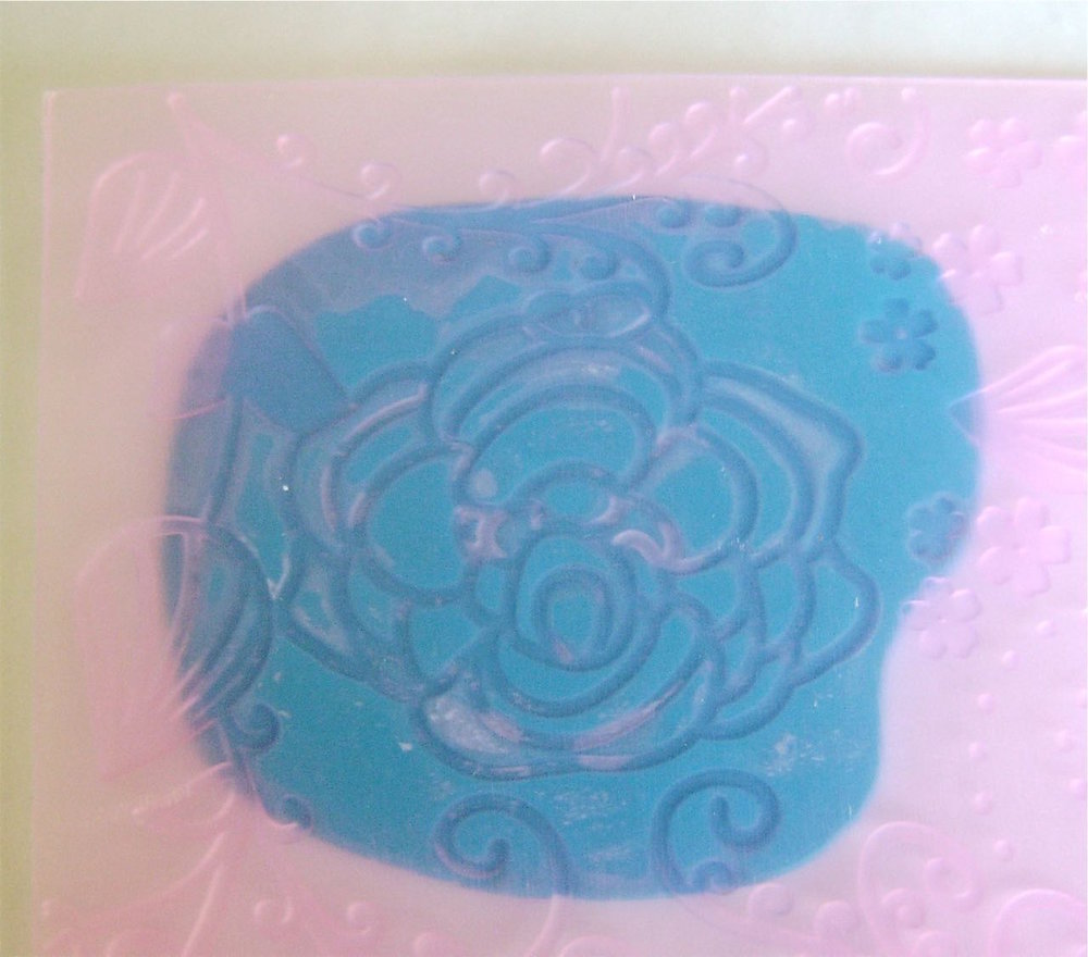 step 2 -Place the rose design portion of the texture sheet onto the blue clay.  Rub across the sheet to transfer the design into the clay.  Remove the sheet.  Create a second piece of clay to match.