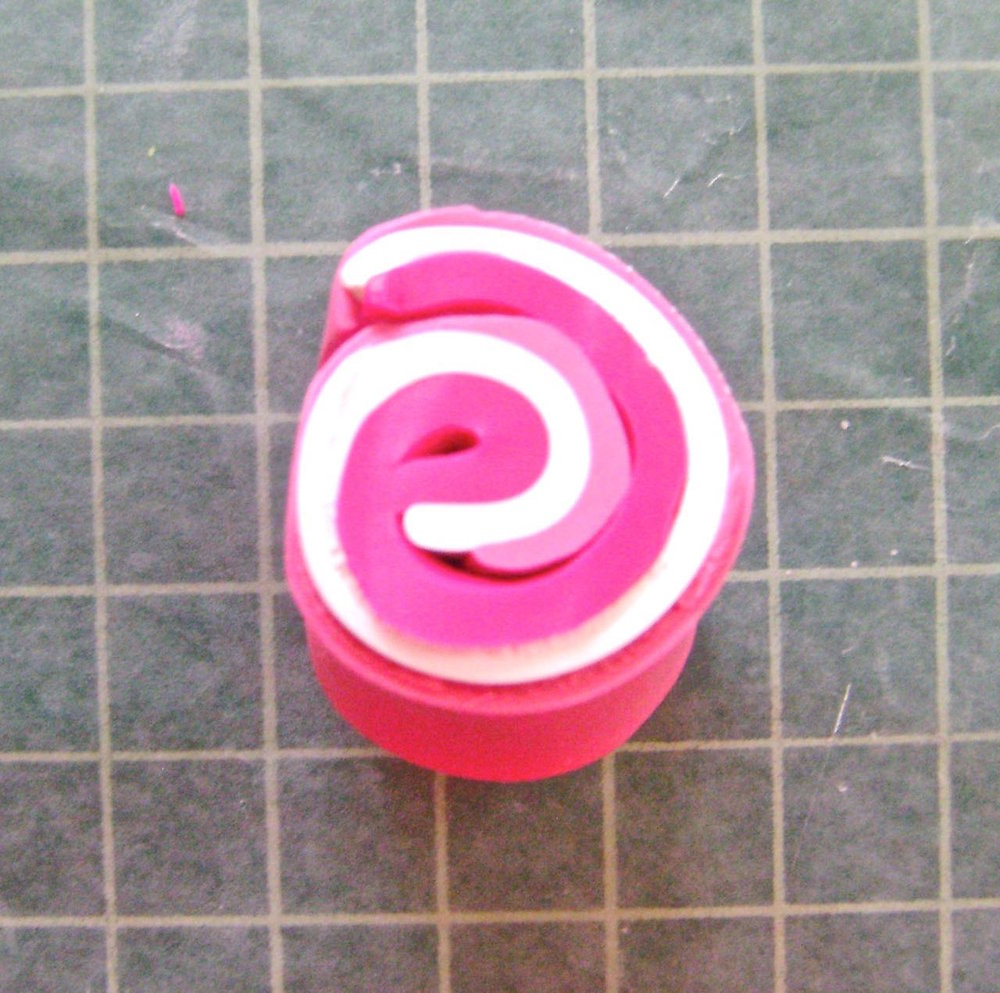 "step 1 - To achieve the dark pink color, roll thin sheets of Fuchsia, Ballerina, and White clay together.  Slice a .50"" wide piece from the roll and run it through the conditioning machine until you reach the blended shade you like."