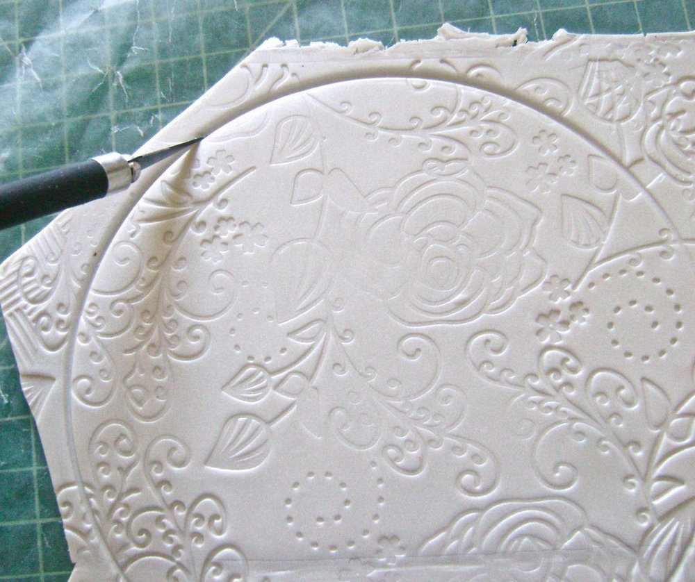 step 7 - Use a craft knife to cut along the round shape made by the lid.