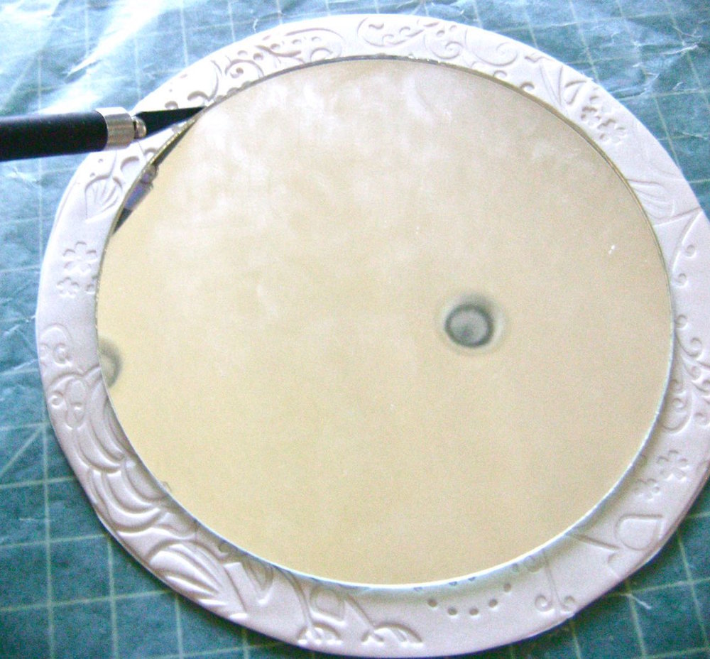 step 8 - Center the mirror on the textured circle.  With a craft knife, run along the edge of the mirror cutting a frame in which the mirror will rest. Remove the mirror.