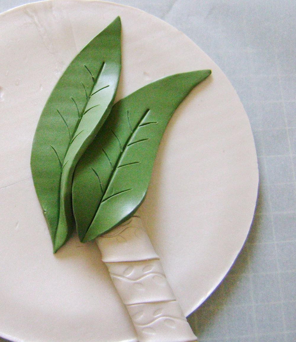 step 11 - Cut out two large leaf shapes from green clay with a craft knife.  Use an Etch n' Pearl tool to create details in the leaves.  Arrange them on top of the handle.