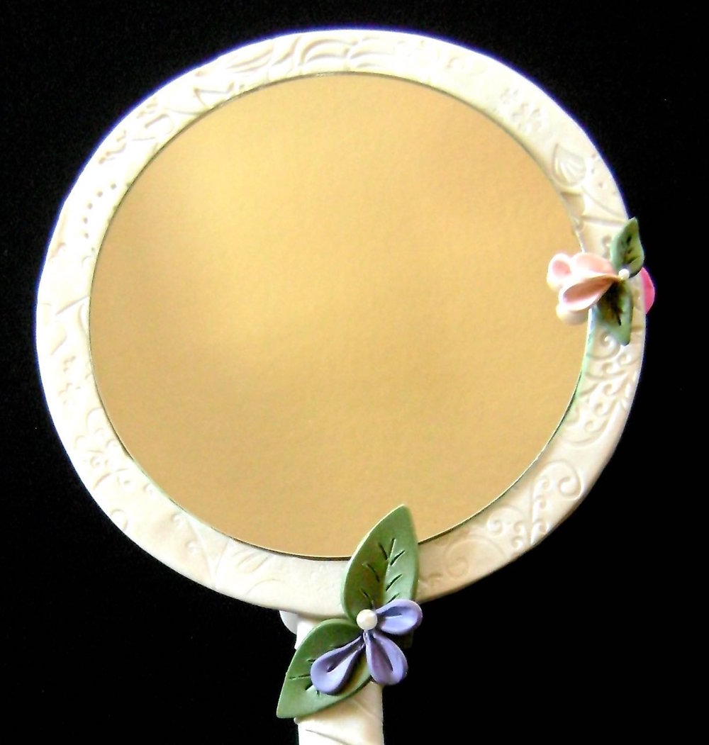 step 17 - Remove the cushion pads on the backside of the mirror.  Use glue to attach the mirror inside theclay frame.  Create a few more petals and leaves to attach to the frame.  Bake them as the others.  Once cool, attach pearls and glue the flowers to the frame slightly overlapping the mirror's edge.