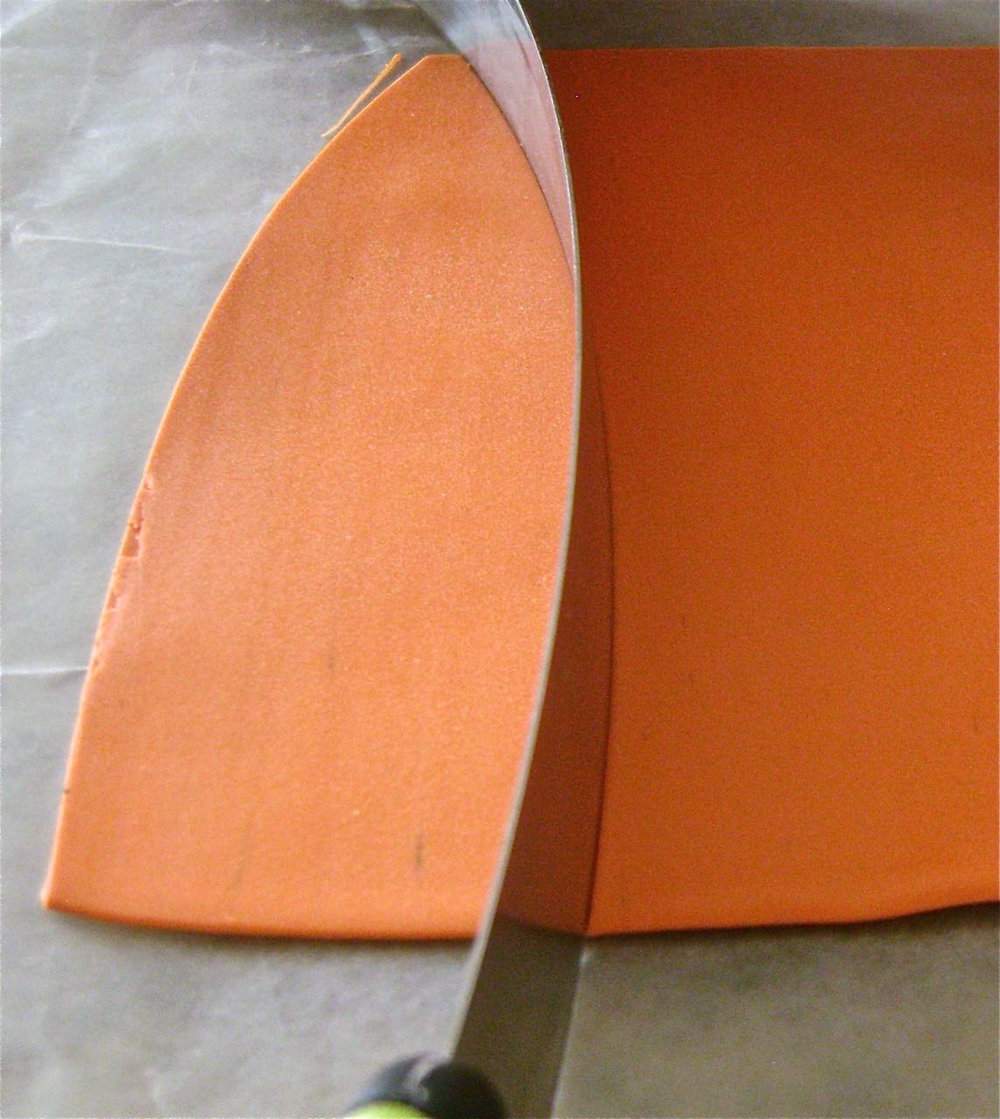 step 2 - Roll out the Pumpkin clay on a number four setting of the conditioning machine.  Cut out about seven identical curved shapes using a slicer blade.  The shapes should measure approximately one inch at their widest point.