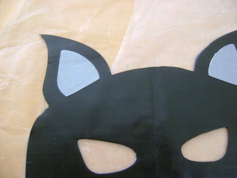 step 4 - Place the mask template on the joined pieces.  Use a craft knife to cut out the mask shape.  Use the template's ears to cut silver ear linings from the clay.  Remove a portion of the bottoms and place the linings on the mask.
