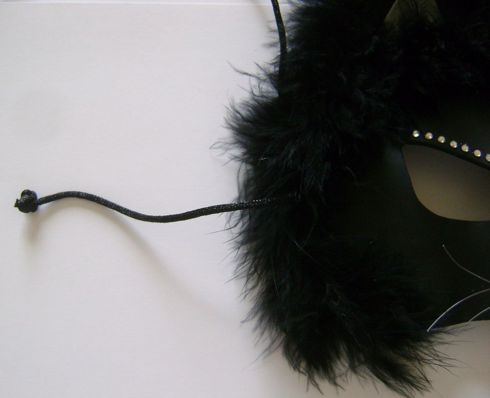 "step 14 - Bring 13"" cord pieces from the back of the mask to the front.  Tie a double knot in each and cut off the excess.  Pull the cord to the back to hide the knot in the fur."