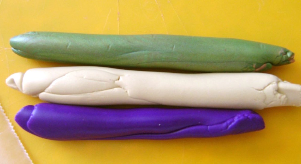 "step 1 - With your hands, make a roll each (about 2"" long) of Ecru, Purple, and Olive Green clay."