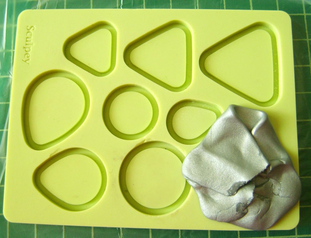 step 1 - Condition 1/2 oz. of silver clay along with small pieces of green, red, and black. Press the silver clay into the largest circle in the mold.