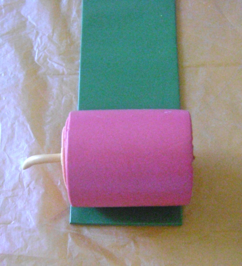 step 7 - Cut a piece of green clay rolled on machine setting #4, to measure the same width as the jellyroll.  Cut the green edge straight and press it against the pink clay.  Roll until the pink is encased in green.