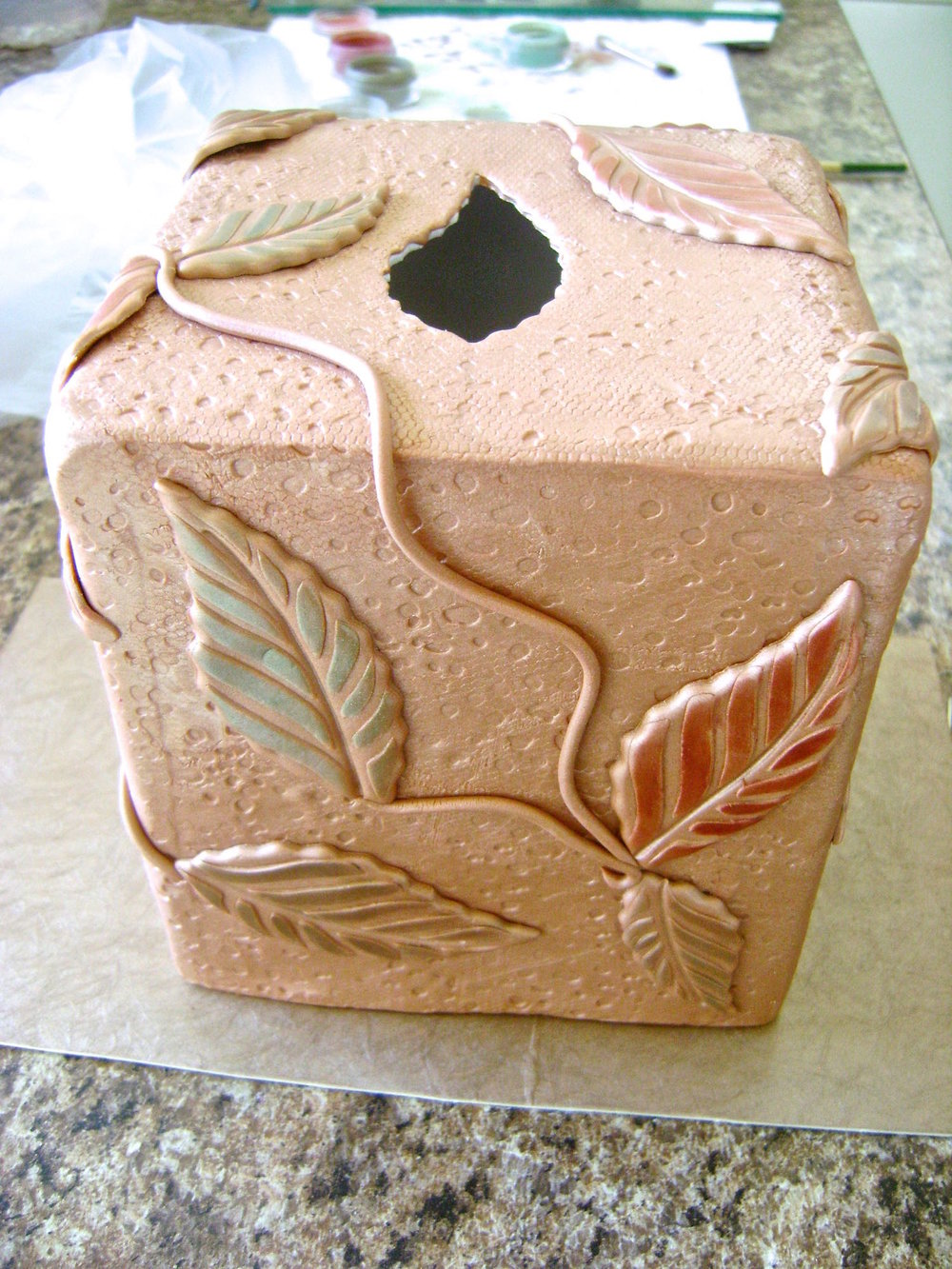 step 11 - Arrange the leavesand vines on the clay box, pressing them gently enough not to distort the design.