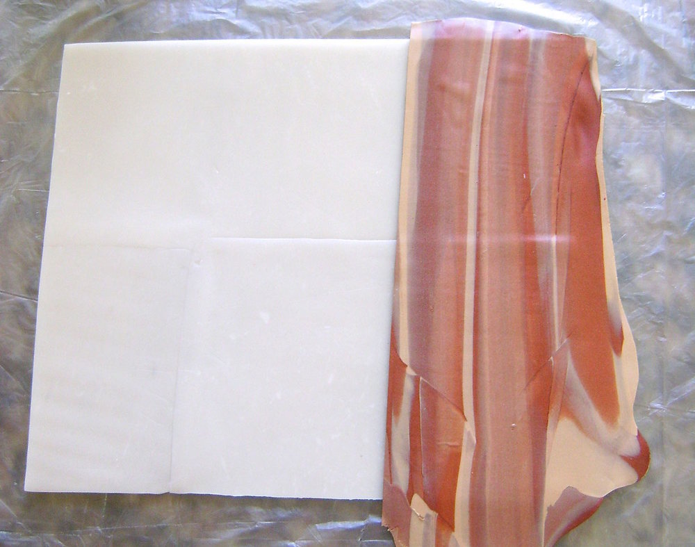 step 6 - Cut a straight side edge on one of the thin layers.  Position it on the large translucent rectangle. Continue adding thin layers, trimming the sides as necessary, until the rectangle is covered.  Blend the seams with your fingers. Place wax paper over the clay and flip it over.  Cut away clay that extends beyond the rectangle.  Turn the clay back to the right side.