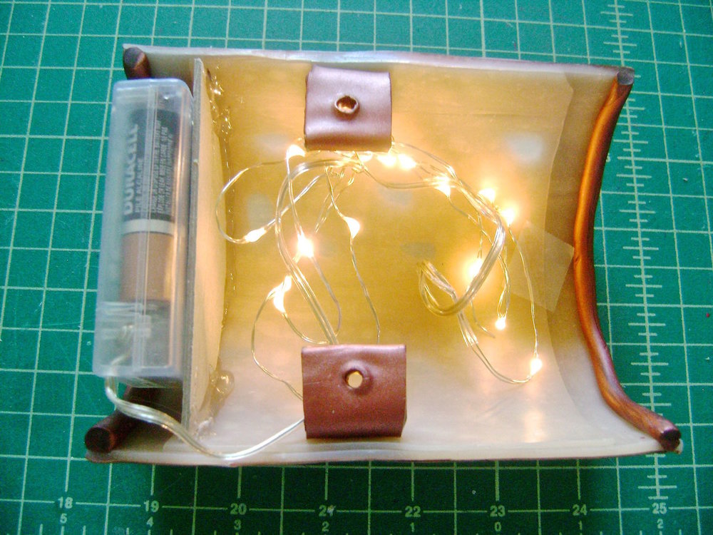 step 16 - Apply hot glue on the tray surface and adhere the battery pack.  Be sure the switch is facing up.  Wind the lightsin a circle and tape the bottom of them to the inside of the sconce to keep them from falling out.  Rearrange the wires if necessary to bring light to all of the leaf cut outs.