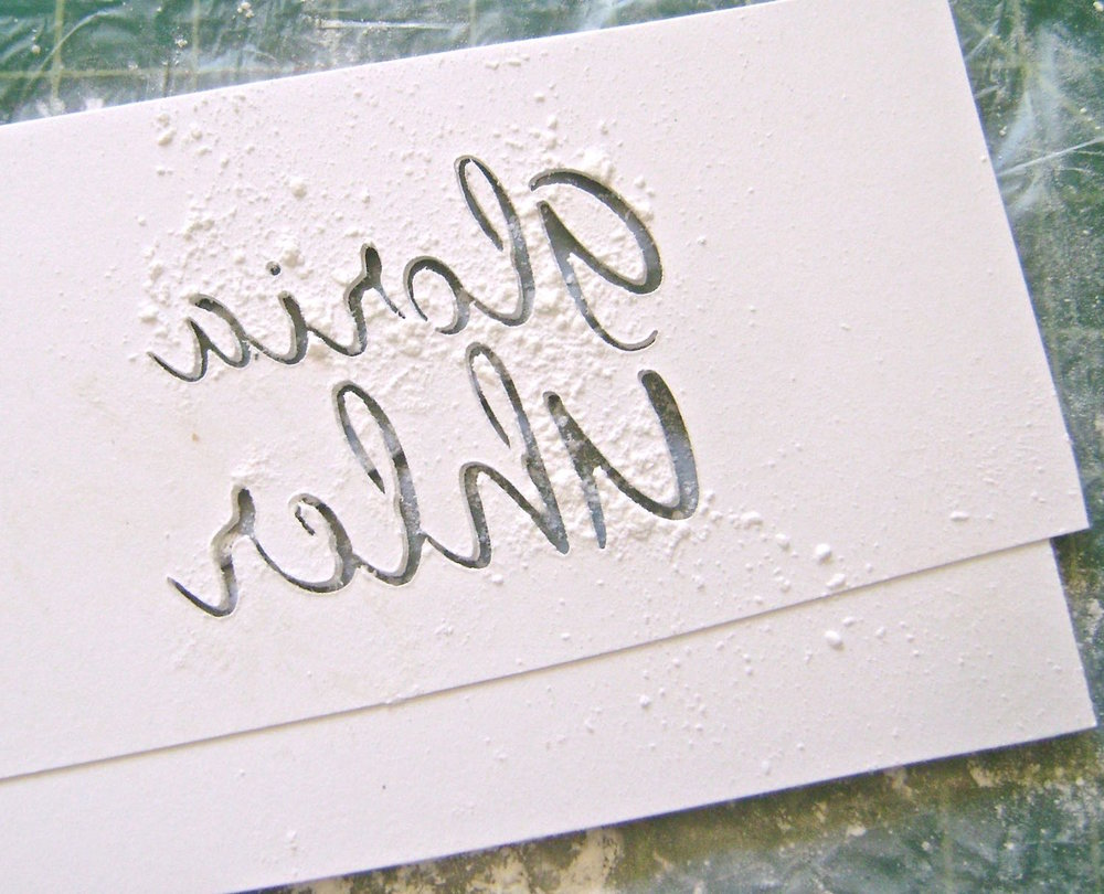 step 3 - Sprinkle baby powder onto a paper towel.  Rub the readable side of the stencil against the powder which will prevent clay from sticking to the card stock. Remember, the signature has to be flipped to stamp correctly.