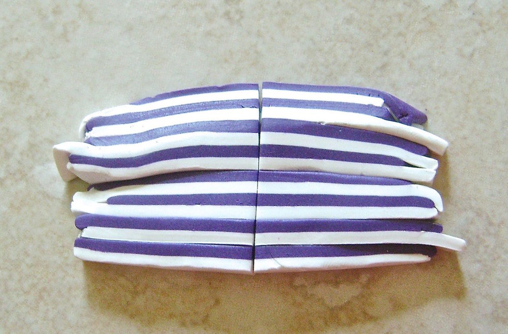 step 6 - Cut a small amount of purple and white clay into strips stacking and alternating them.  Continue cutting in half and stacking until you have a thin striped strip to fit at the base of the hat.