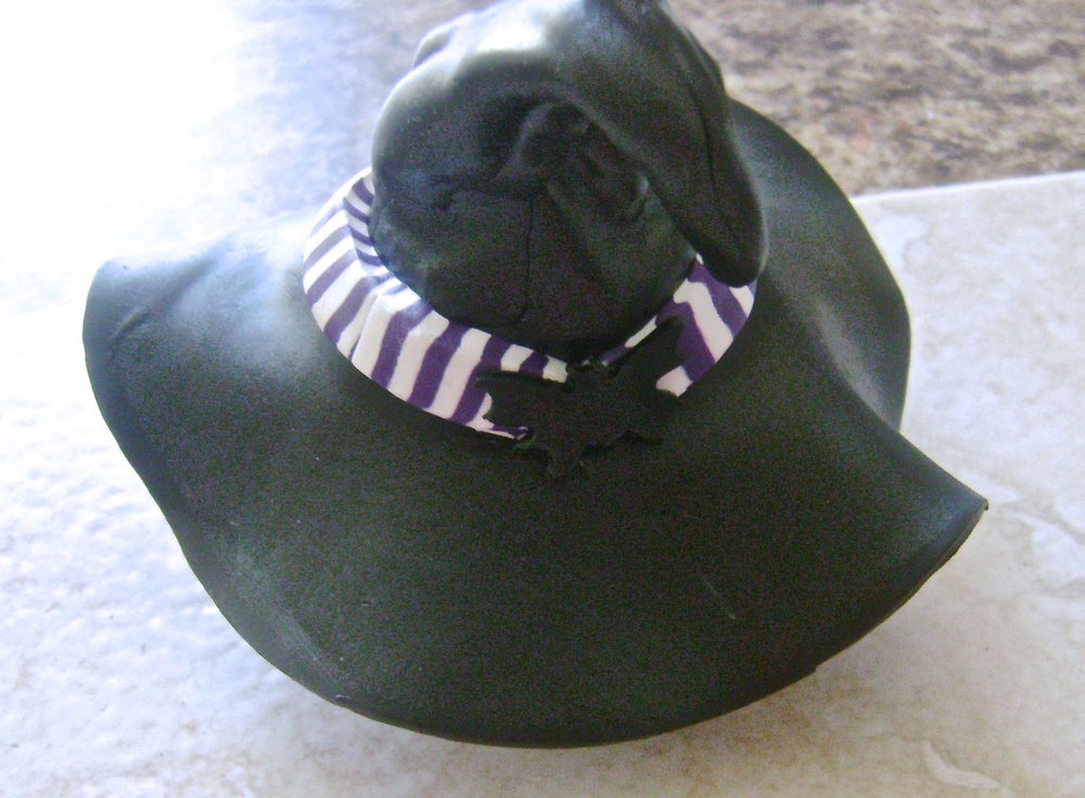 "step 8 - Place the hat on the 1.25"" cutter for support while baking in the oven.  Press a bat onto the striped band.  Insert clumped up foil under the brim to retain it's shape.  Without support the brim will droop and the hat won't seat on the ornament properly."