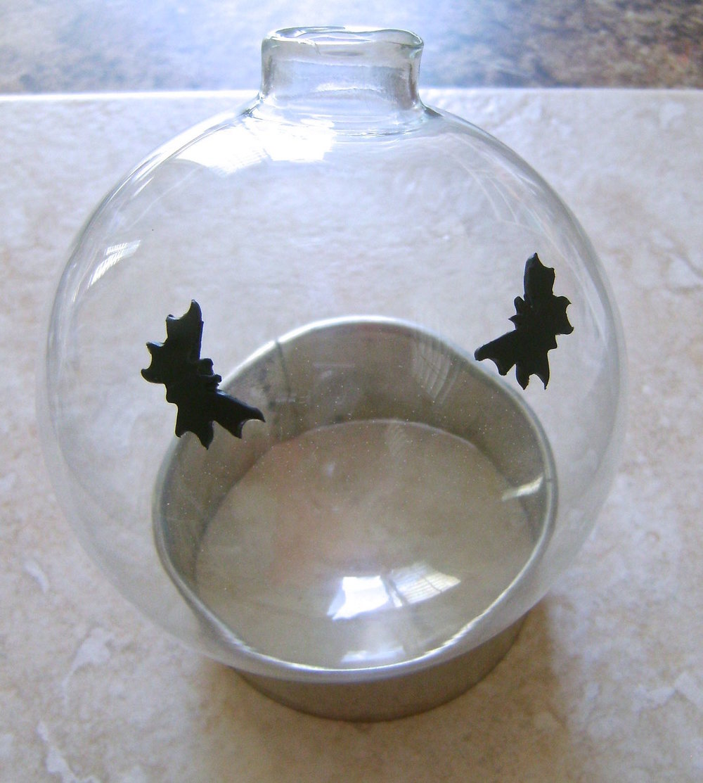 Step 9 - Plan your witch placement (see step 11) on the ornament and press bats on the glass to surround them.  Set the ornament on a large round cookie cutter for support while baking.
