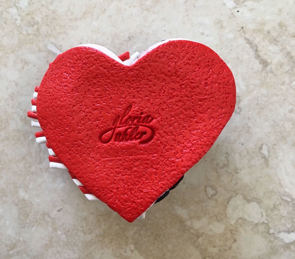 step 10 - Add texture to a piece of red clay with rough sand paper. Cut it out with the large heart cutter and press the red clay over the white clay. The texture will prevent the pendant from sticking to your skin when you wear it.