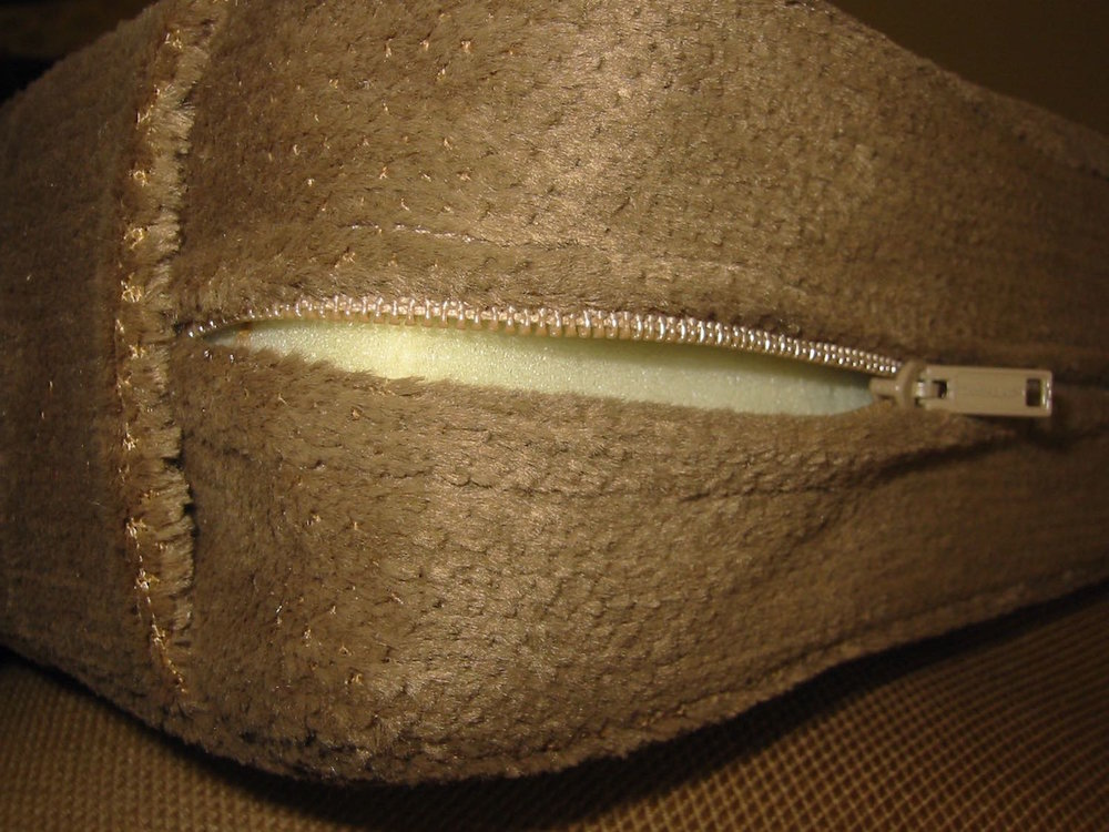 step 11 - The folds in the side pieces allow the zipper ends to remain tucked away and hidden from view in the bottom sides of the bolster. Sew the raw edges of the side pieces to the edges of the top piece with right sides together.