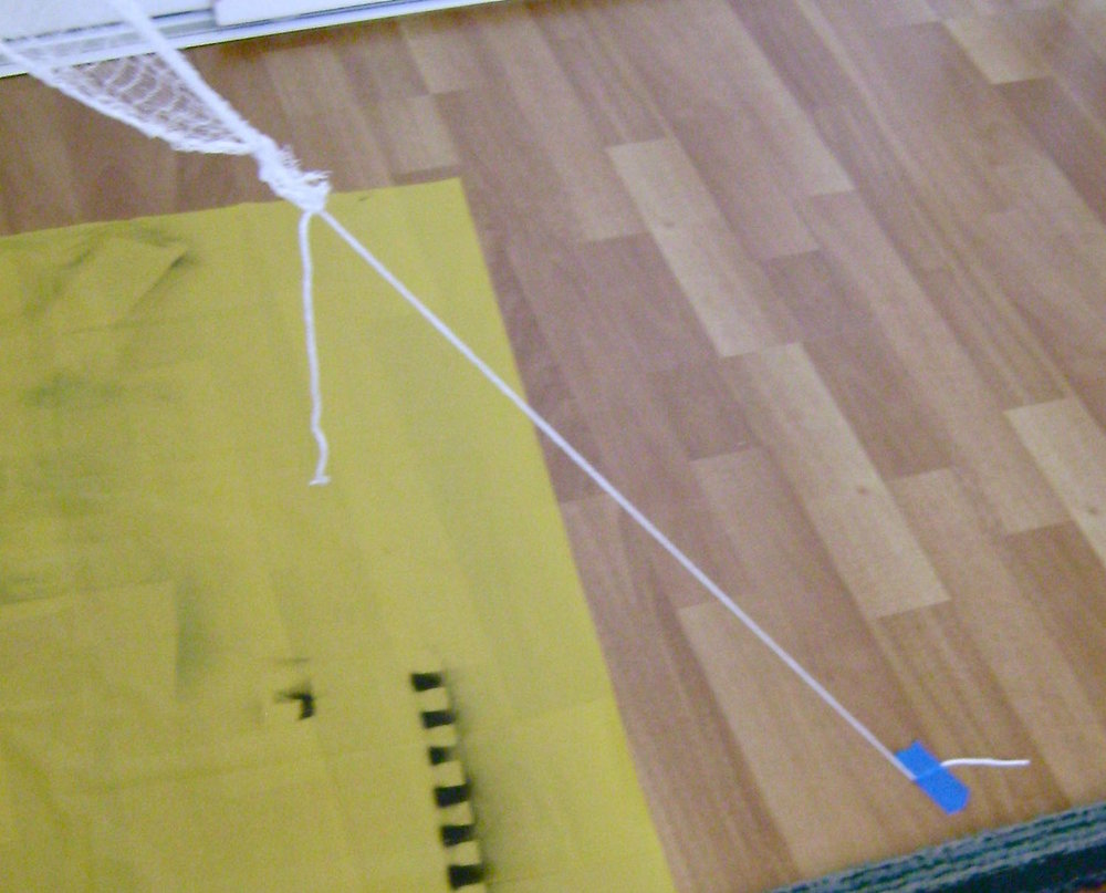 step 7 - Tie a piece of string or yarn to eight corners of the cloth.  The string/yarn should be long enough to reach the floor or a nearby stationary object.  Using painters tape, secure the string/yarn with the cloth stretched out in different directions.