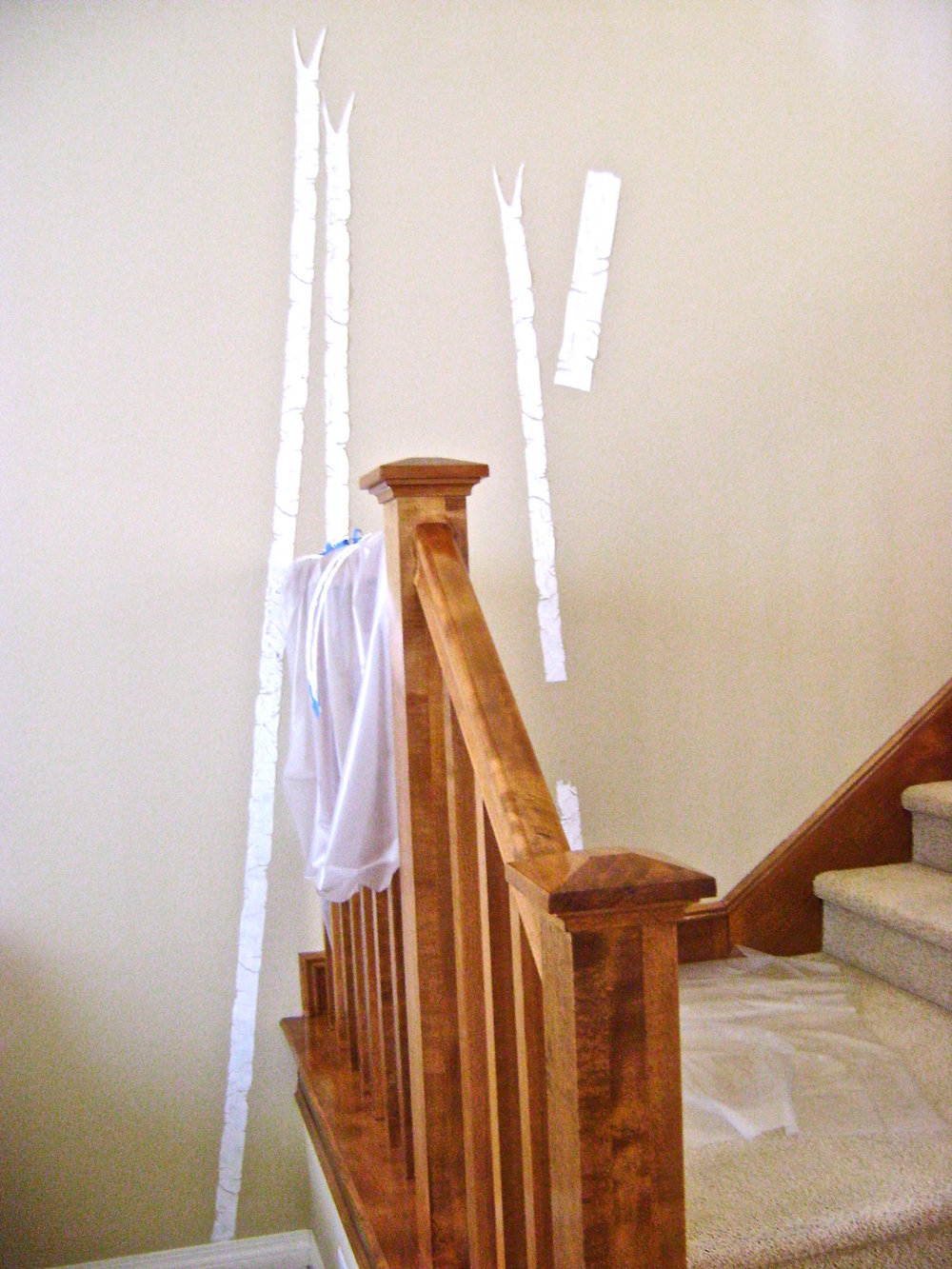 step 4 - Create all the tree trunks first by adding additional sections as you work up the wall and reach the desired height.  Hold the stencil to the wall with painters tape.