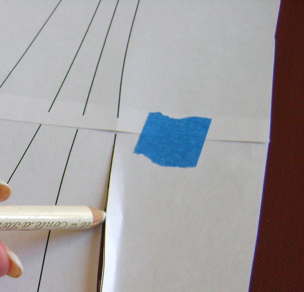 step 4 -  Position the template on the canvas.  Using a chalk pencil, draw light lines in the slits and dots in the circles.