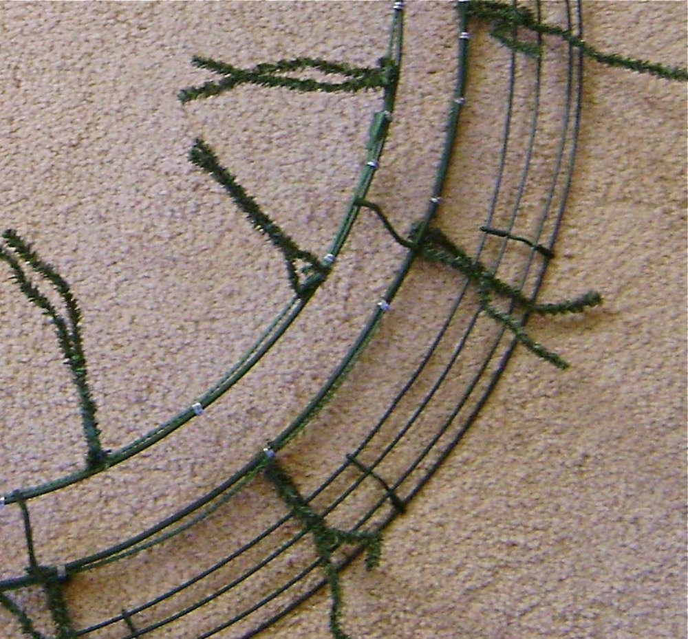 step 4 - Add 4 rows of garland working in a circle.  Begin at the outside of the wreath ( # 1) attaching garland to the outer most wire of the larger wreath. Use the excess ends of the twist ties to connect the garland.