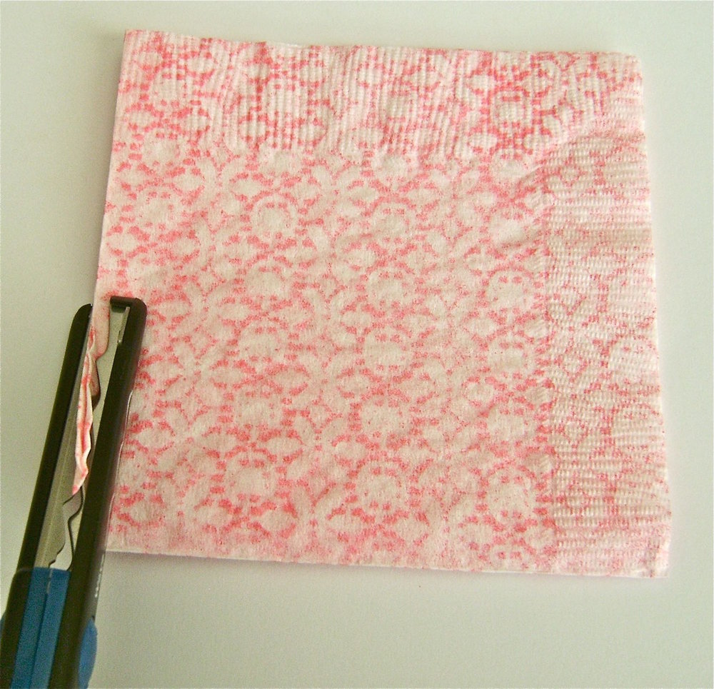 """step 2 - Return the napkin into the original folds creating a 5""""x5"""" square. The folds should be on the left and at the bottom. Trim left and right outer edges with decorative edged scissors."""