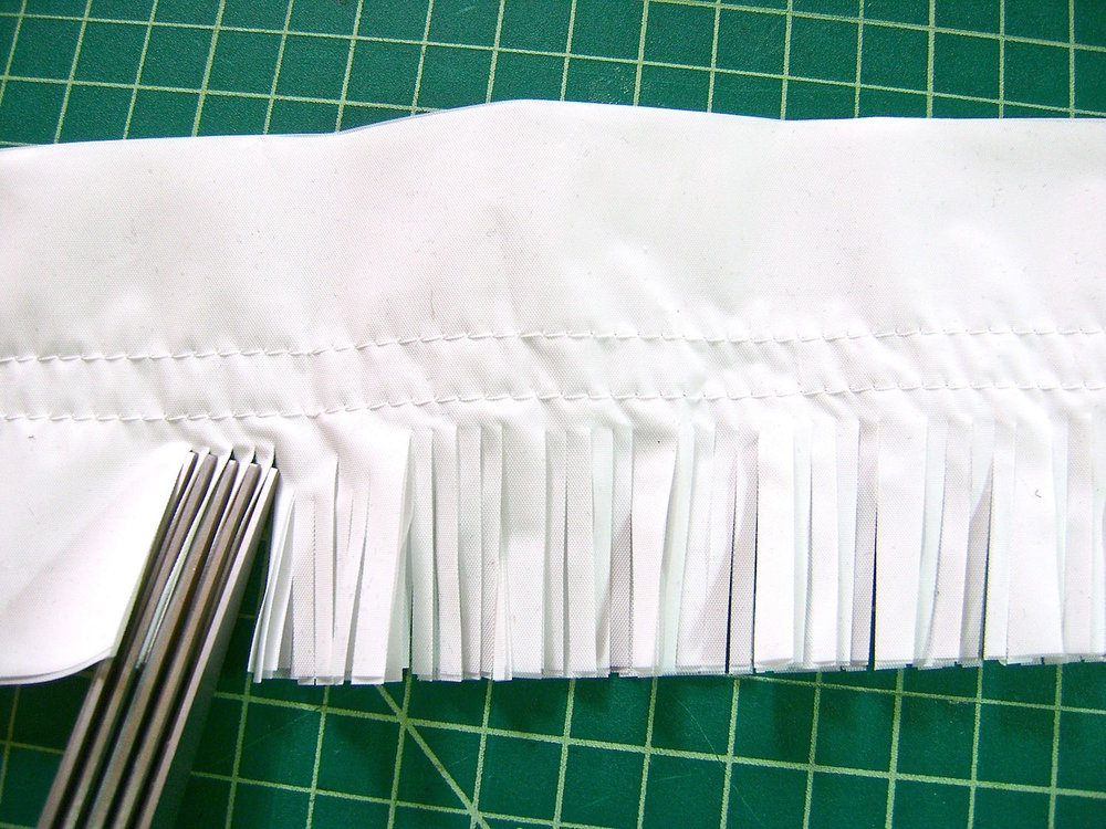 step 5 - Fringe all the sets using the special fringing scissors. Cut from the outside edge into the center, close to the stitching but not through it.  You can stack the sets and comfortably cut through two sets at a time.