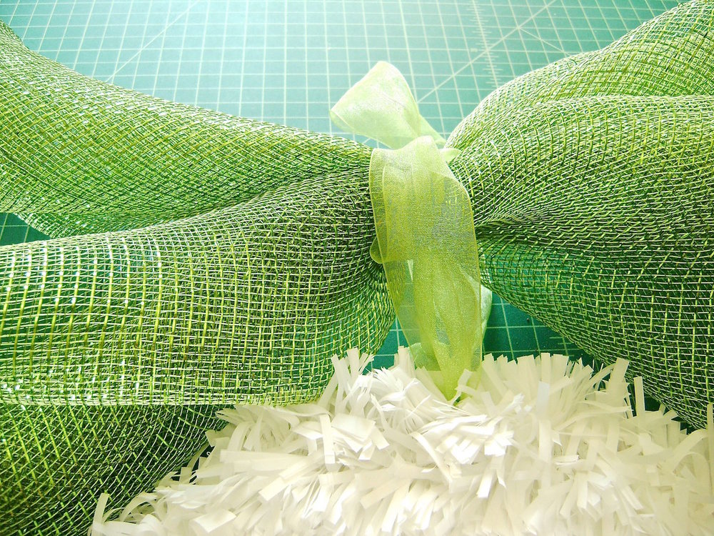 "step 10 - Cut two pieces of deco mesh to 30"" long.  Fold them diagonally and roll them up. Tie them together at the center with ribbon. Attach them to the ribbon on the egg."