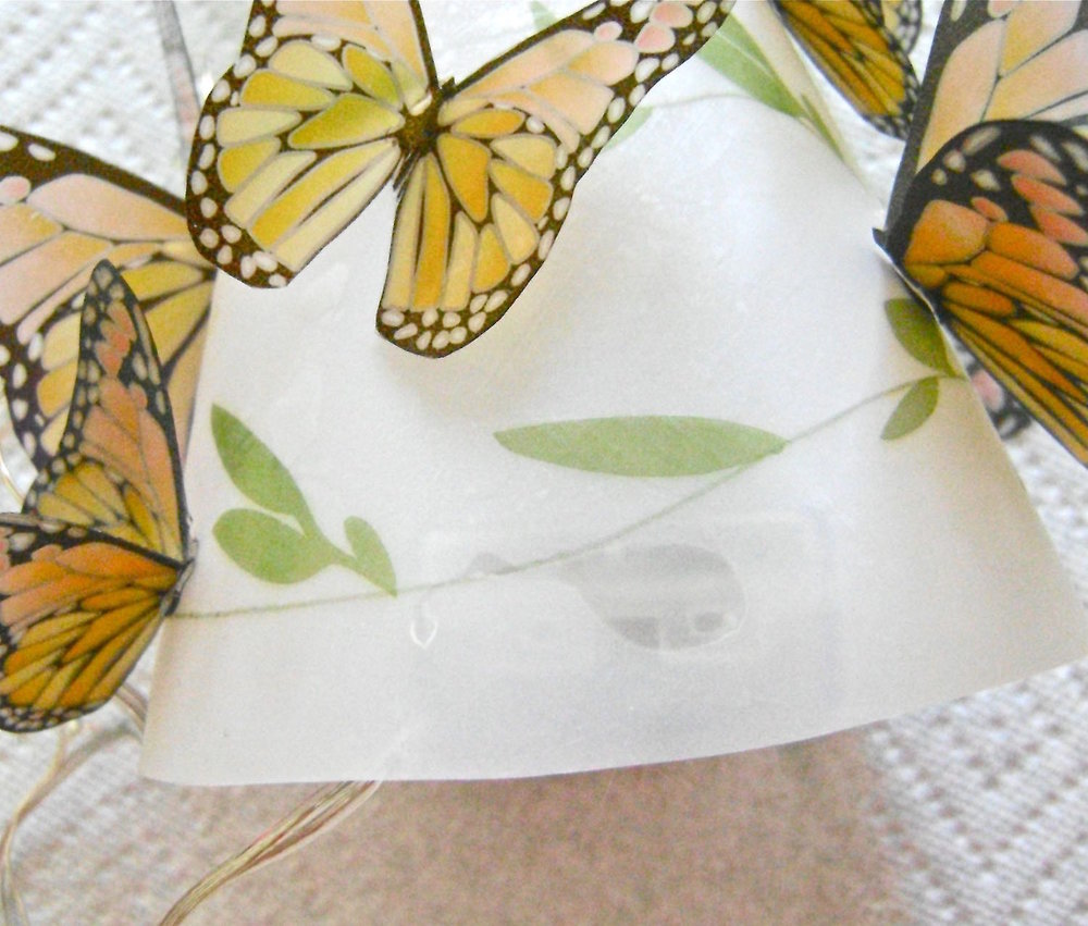 step 11 - To hide the spot where you hot glued the shade to the battery pack, attach a small butterfly.  Stuff the lights inside the shade and enjoy your lamp!