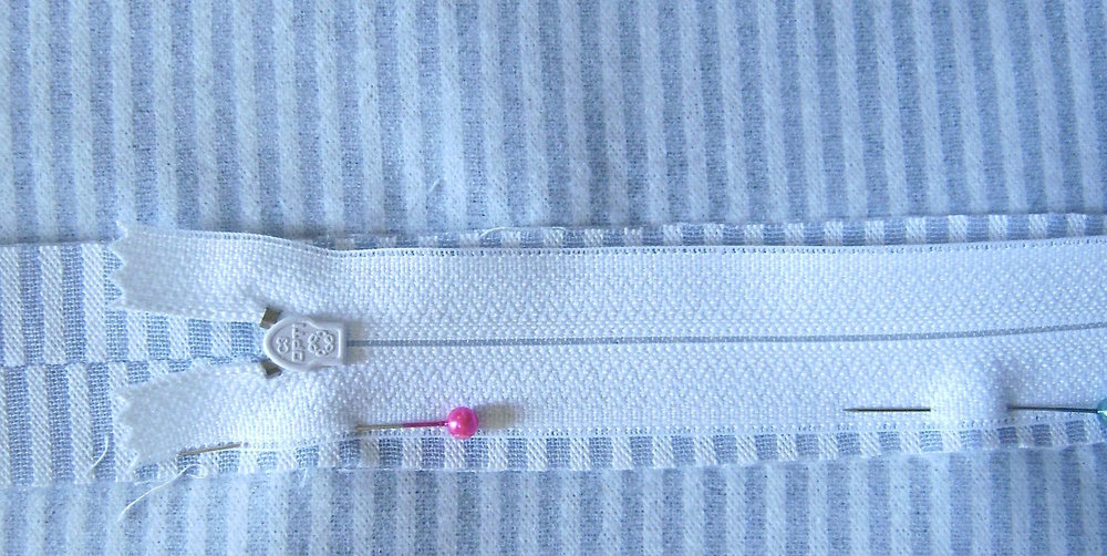 step 2 - Press the seam open. Center the zipper over the center of the seam.  Pin the zipper to the seam and stitch in place on the right side of the fabric.
