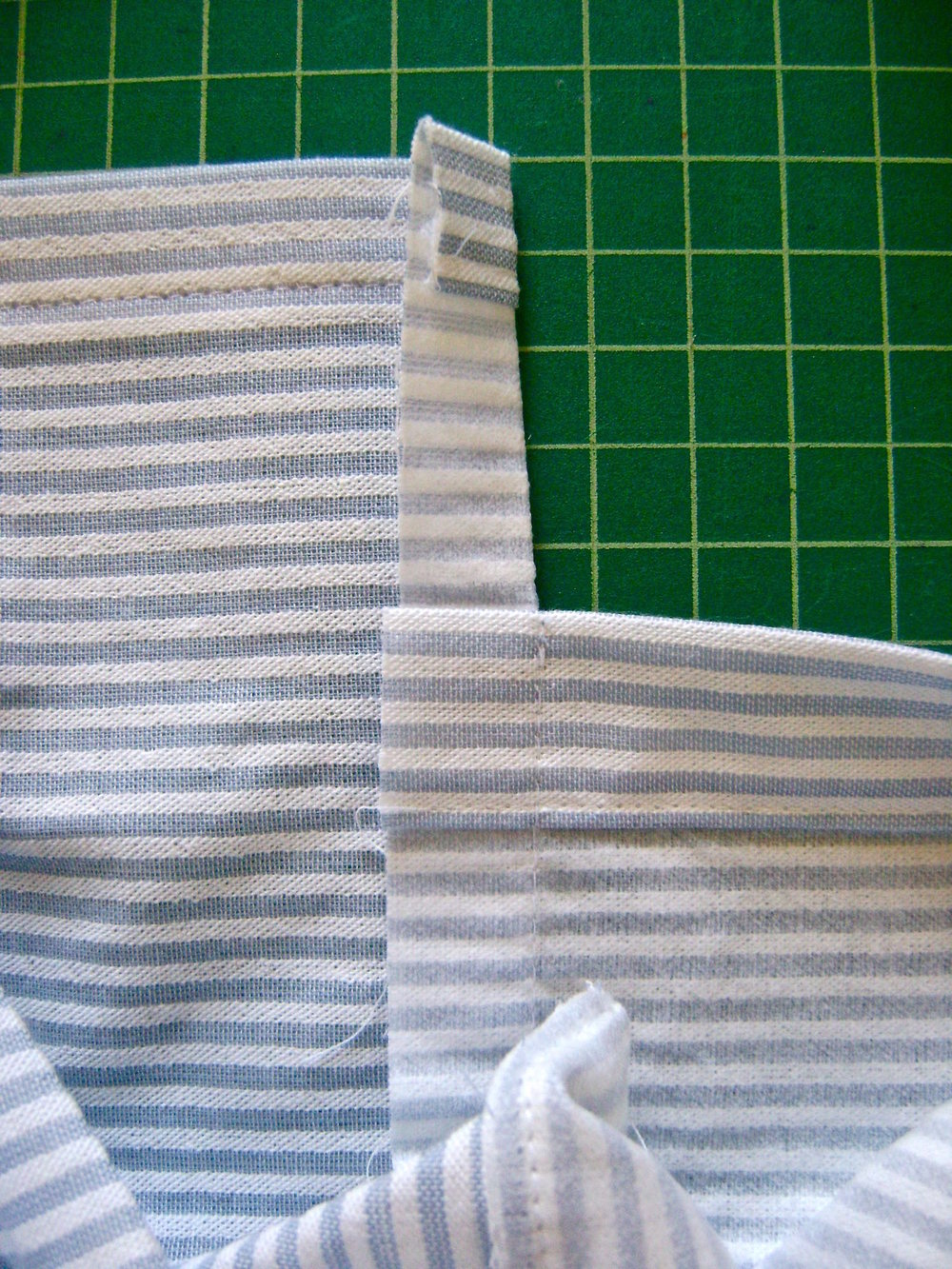 "step 11 - Press the side seams to the pocket back.  Trim the seam allowance to one quarter inch. Turn the pocket right side out.  Top stitch across the bottom 3/8"" from edge."