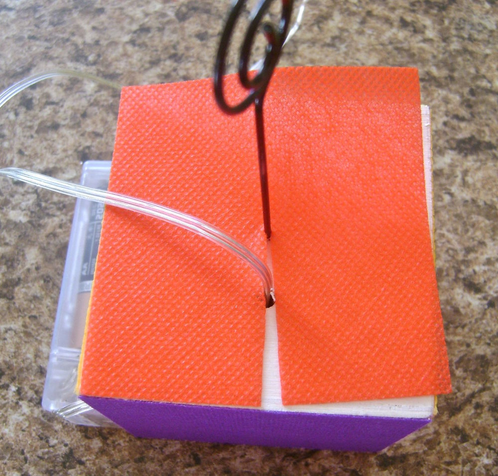 "step 6 - Apply a gold ""X"" on three of the fabric squares with Beads In A Bottle.  When dry, attach silver stars in the center with hot glue.  Attach the gold ""X"" squares to the front and two sides of the cube with the glue stick.   Glue a plain square to the bottom of the cube.  Make a cut halfway through the remaining square and slip it around the light string and photo wire on the cube top.  Bring the slice together and glue in place."