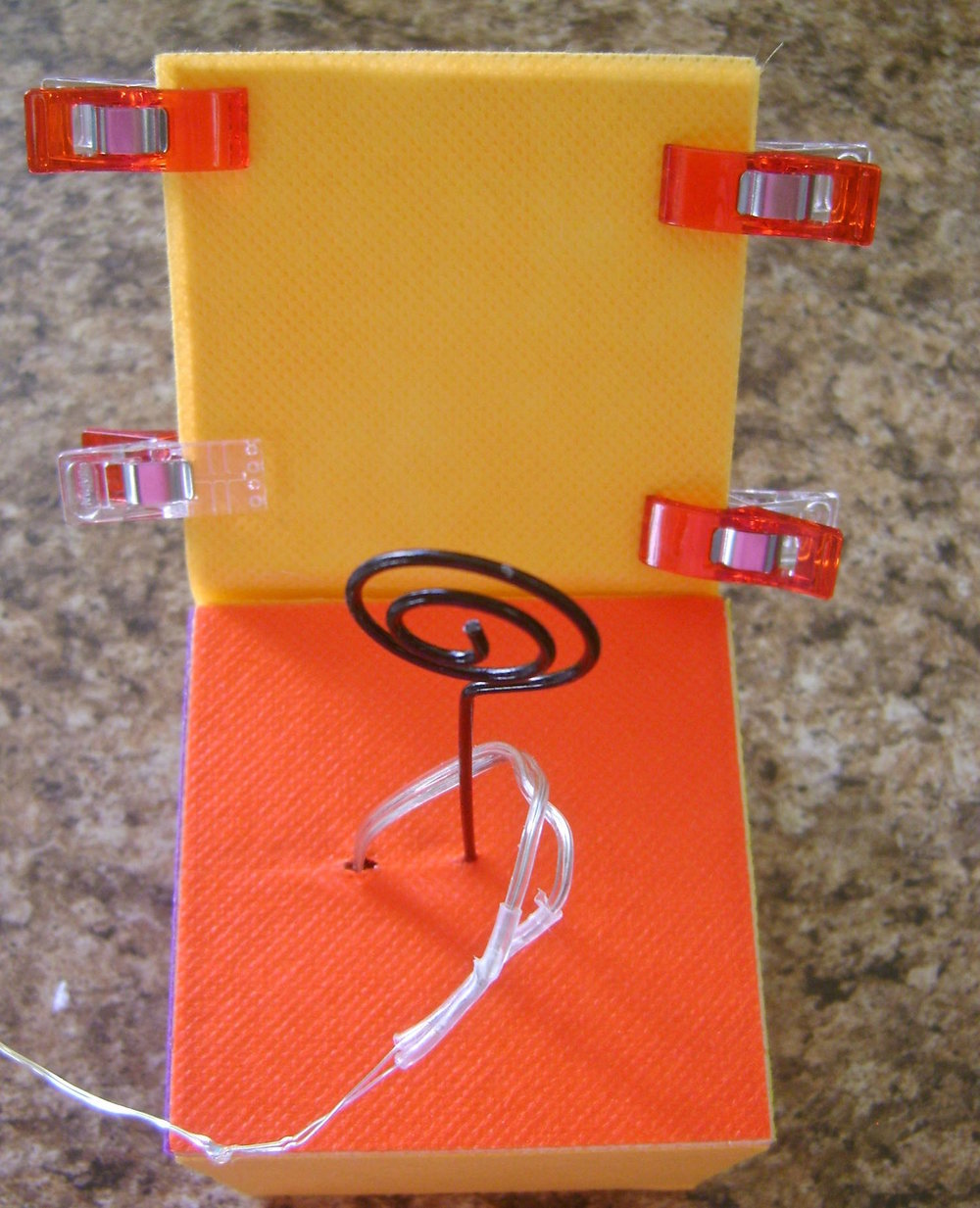 "step 7 - Create the back flap by cutting two fabric and two card stock pieces to measure 3"" x 4.25"".  Use the glue stick to sandwich the card stock pieces inside the fabric pieces.  Glue the layers to the back of the cube just above the battery pack.  Use Wonder Clips to hold the layers together until they dry.  Bend the flap back at an angle.  Hot glue silver stars in each top corner."