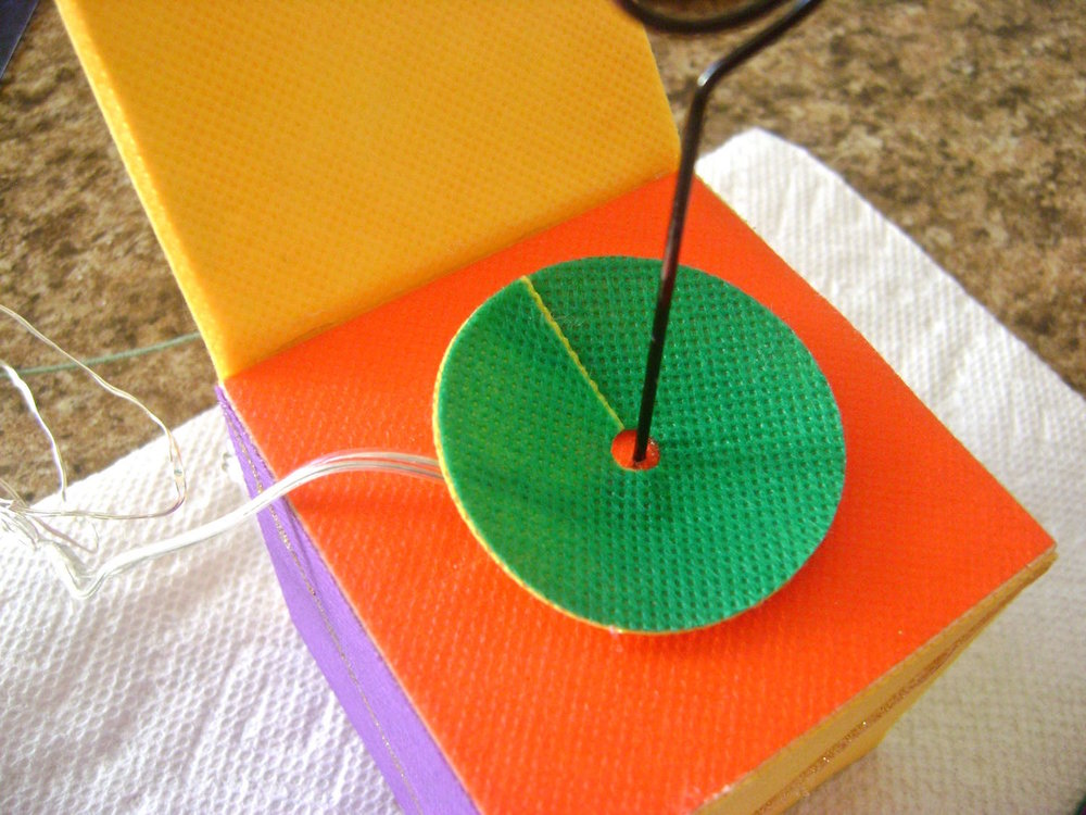 step 11 - Slip each disc around the photo cube wire.  Overlap the ends until the disc curves upward or down and hot glue the ends together.  Repeat with all seven discs stacking them on the wire.