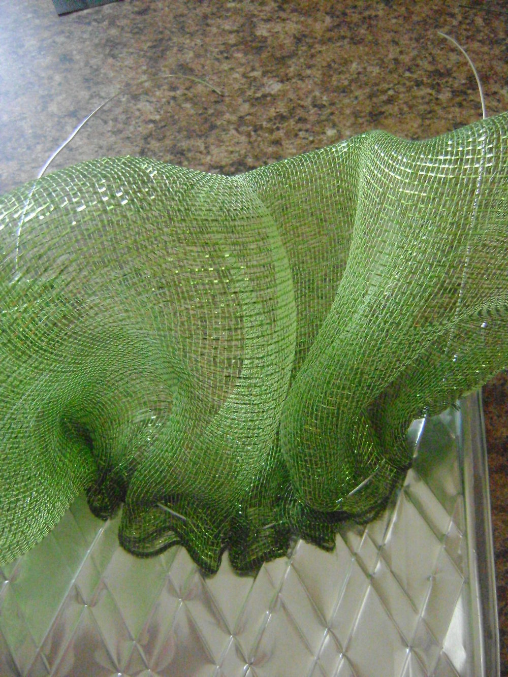 "step 6 - Gather the mesh in the center of the wire leaving 9"" leads on each end for the hanger.  Apply a heavy glob of hot glue on the mesh ends to keep them from slipping across the wire. Align the wired mesh with the curve of the embossed foil.  Hot glue the mesh to the foil starting in the center and working out to the edges."