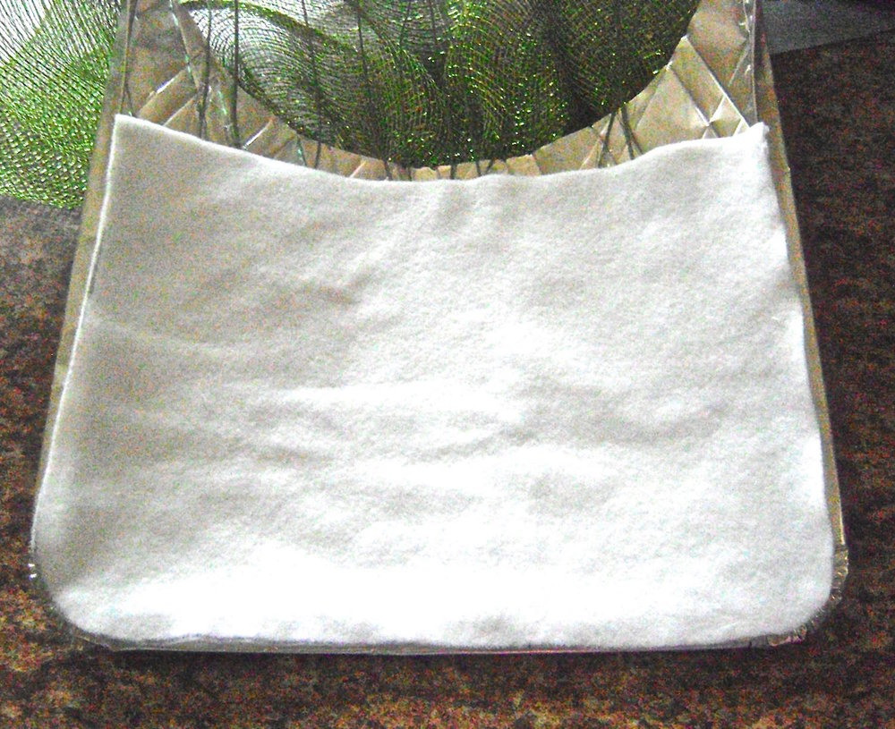 step 14 - Fold the edges of the foil flat and trace the shape of the bottom and sides to create a template.  Use the template to cut a lining out fleece, felt, or other soft fabric. Hot glue the lining to the foil back.  The fabric will prevent the foil from scraping the finish on your door.