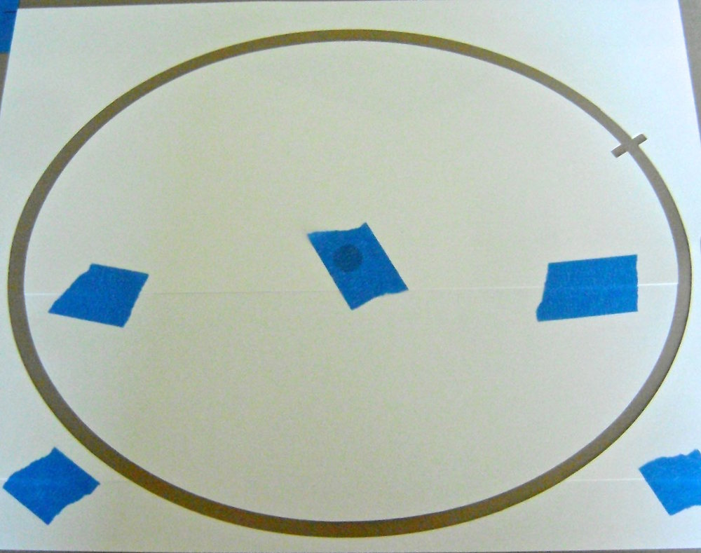 "step 7 - Cut a 11"" X 8.50"" oval out of card stock using a craft knife.  Cut away one-quarter inch from the edge of the inner oval creating a .25"" space between both pieces."