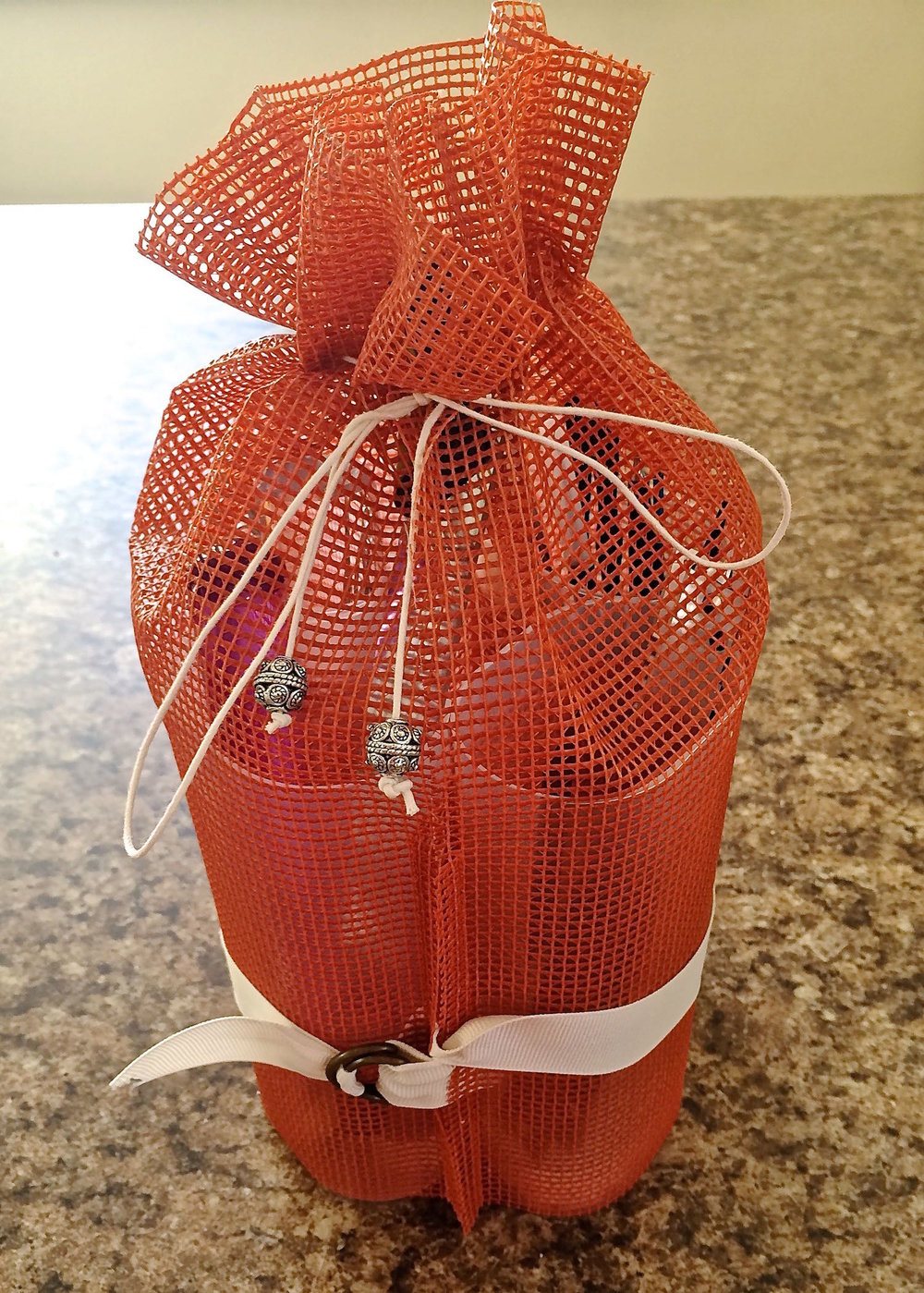 step 10 - Prepare the package for travel by flipping up the fabric back (cuff).  Turn the containers in toward each other and secure them with the ribbon.  Pull on the drawstrings and tie the ends together.