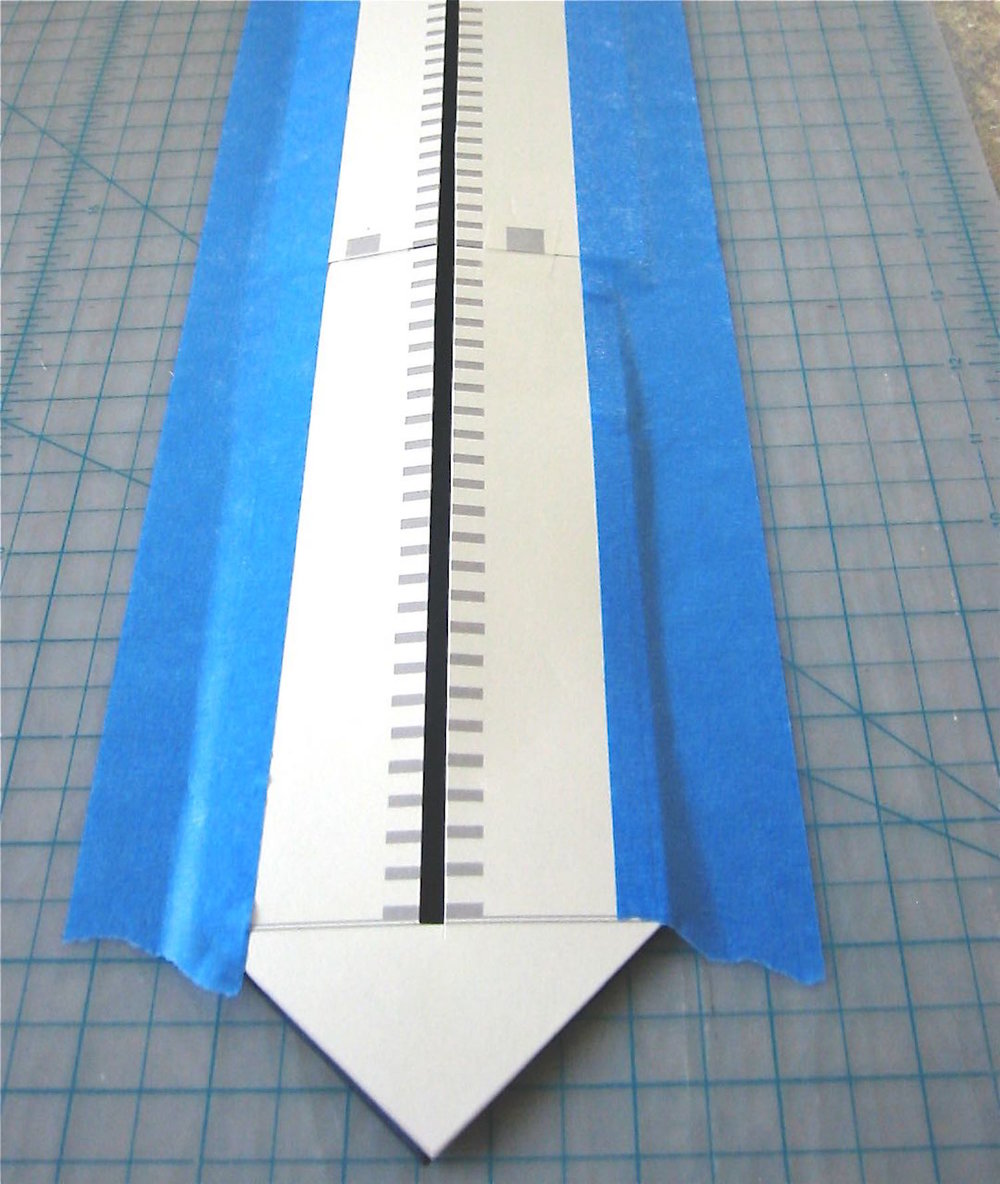 step 2 - Place a hard work surface (like a cutting board), on an ironing board.  Match up the large angled edge of the tie with the angled edge of the template, making sure the center of the template matches the center of the tie. Use painter's tape to secure only the very outer edges of the template and tie to the work surface so it doesn't shift.