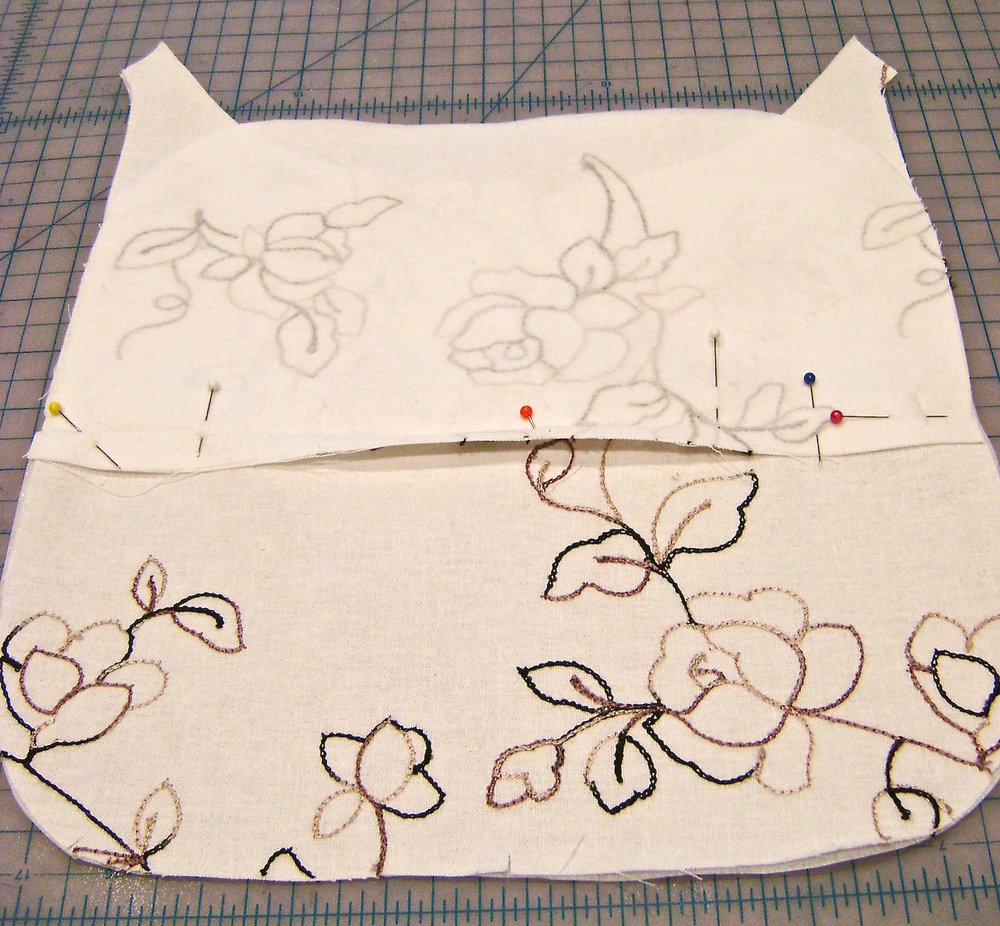 Back Zippered Pockets step 1 - Press the seam allowance on the interfaced pocket piece.  Align the piece as indicated on the pattern with right sides together and the pocket above the dotted line.