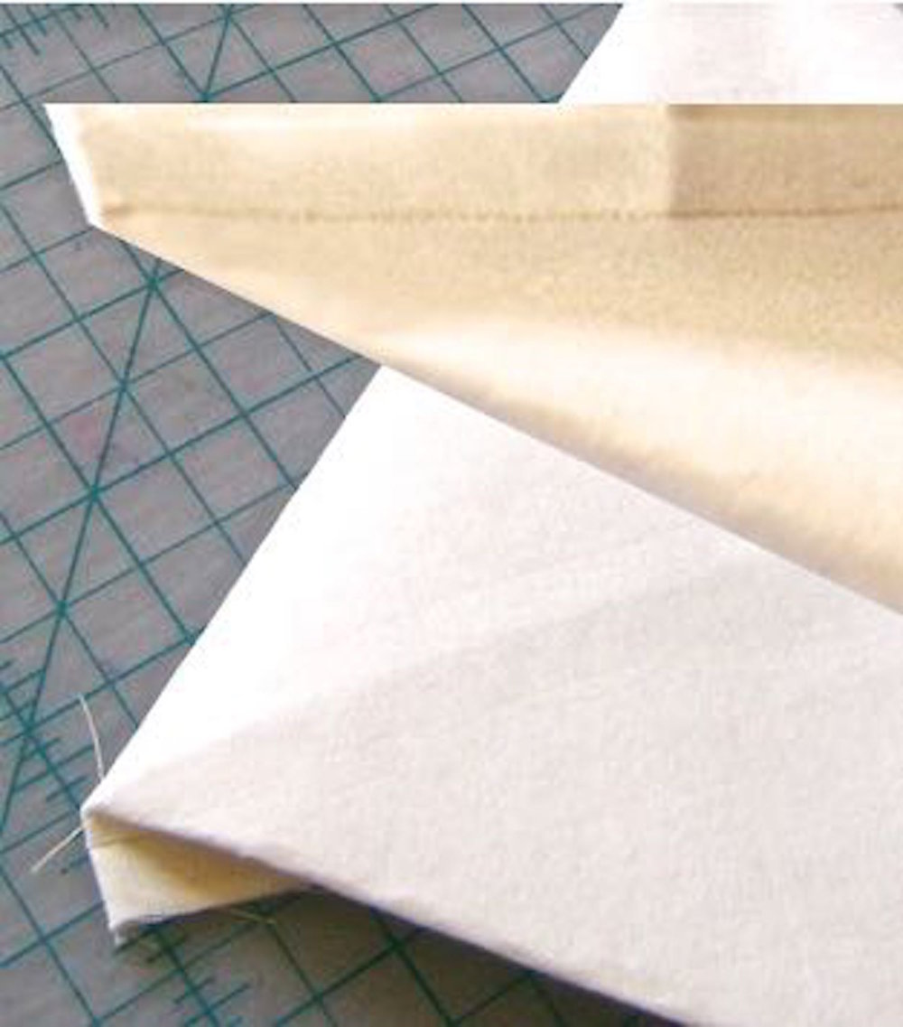step 5 - Bring together the bottom point of the right and left seams in a pyramid shape. Smooth layers. Press with your hands to create temporary creases on angled edges.