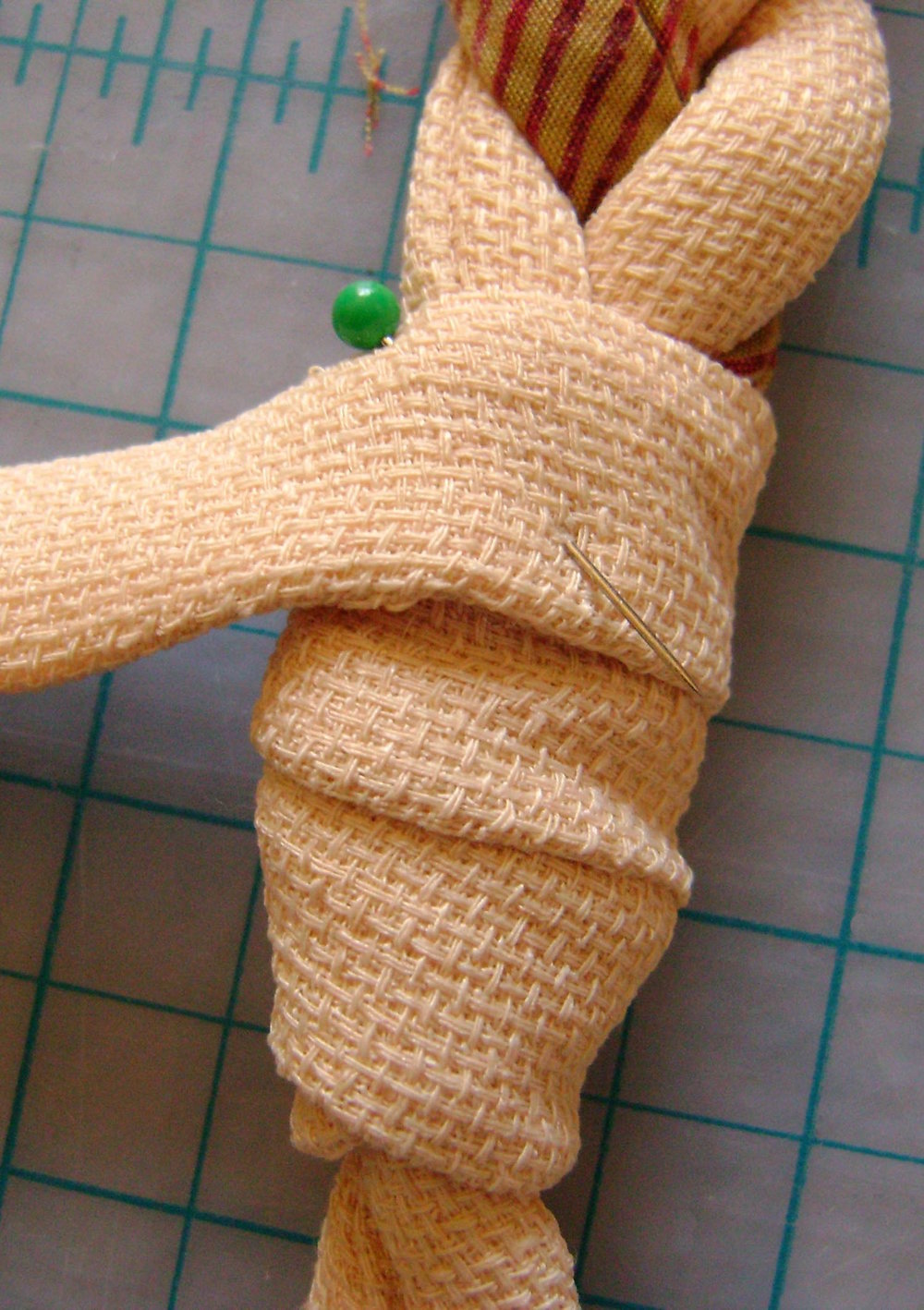 "step 4 - Hide the connection and raw edges by sewing a 3/4"" wide by 6"" long flat piece of fabric to the loop slightly below the point where it connects to the braid. Wrap around, angling upward until the raw edges are covered. Pin in place."