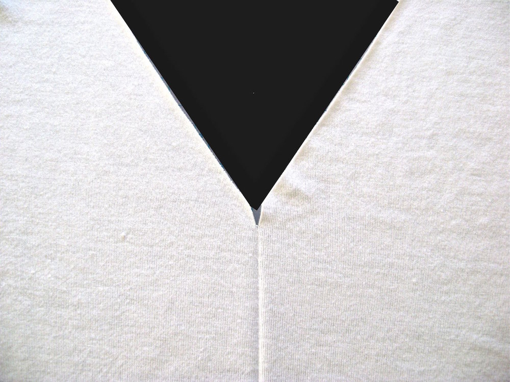 "step 1 - Fold the shirt front in the center and press in a soft crease extending about 4 inches down from the point of the ""V"".  Snip a ½"" opening in the point of the ""V""."