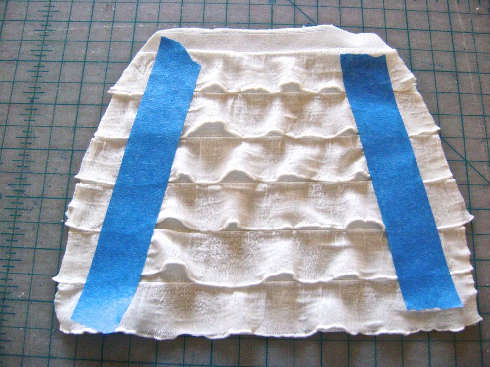 step 1 - Download and print the purse pattern.  Use it to cut out two ruffled pieces, two fleece pieces, and two satin lining pieces.  Taping the ruffles down will prevent them from shifting while you cut.  The bottom edge of a ruffle row should align with the bottom edge of the pattern.