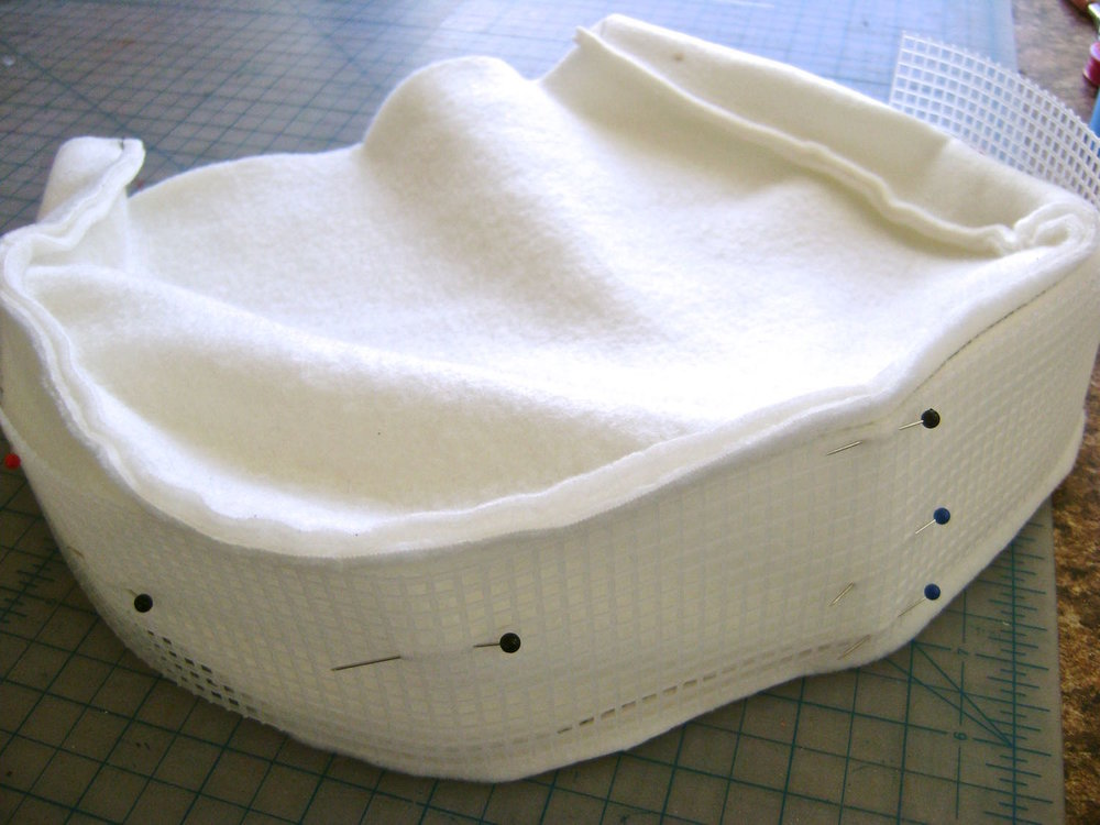 step 21 - Assemble the fleece padding by sewing the front and back to the side and bottom piece.  Match the center of the mesh piece to the center bottom of the fleece's wrong side.  Stitch the mesh to the fleece.  This can be carefully done on the machine with a stitch length to match the mesh or by hand.