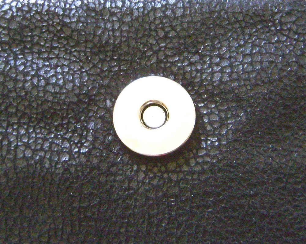 step 28 - Slip the lining over the purse with right sides together.  Stitch around the top sewing the lining, fleece and outer purse shell together.  Trim seam.  Stitch over the flaps again for reinforcement.  Pull the purse out of the lining opening.  Top stitch the seam to the lining.  Center half of the magnetic snap to the front of the purse.  Push the prongs through the outer purse and fleece layers.  Attach the back of the snap between the fleece and lining.