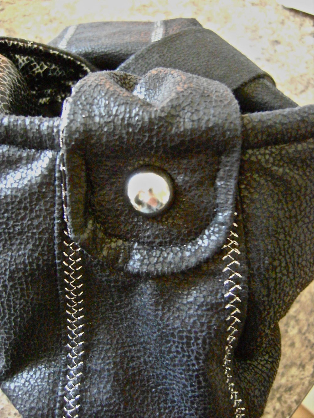 step 30 - Attach a decorative silver stud to the center of the loop.  Push the stud through the purse shell and fleece.  Attach the back side of the stud between the fleece and the lining.
